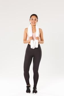 Esporte, ginástica e conceito de corpo saudável. comprimento total de sorrindo linda garota magro, instrutor de fitness ou desportista após exercícios no ginásio, em pé com uma toalha enrolada no pescoço, fundo branco.