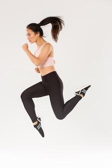 Esporte, ginástica e conceito de corpo saudável. comprimento total do corredor feminino focado sério, tiro de movimento da garota correndo no ar, treinamento de aptidão de bonita desportista magro, treino de atleta em uso ativo.