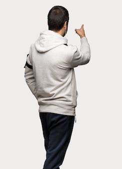Esporte homem apontando para trás com o dedo indicador sobre fundo cinza isolado