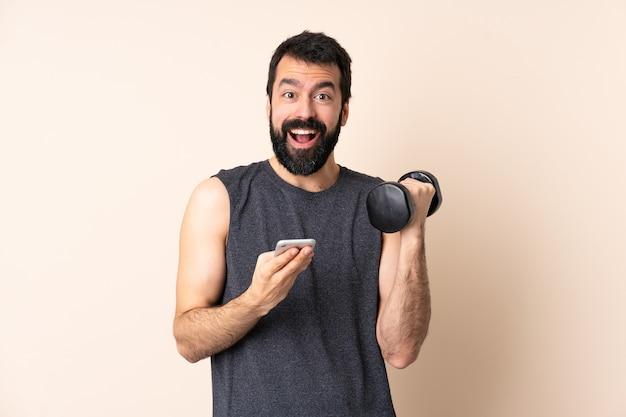 Esporte homem caucasiano com barba fazendo levantamento de peso em parede isolada surpreso e enviando uma mensagem