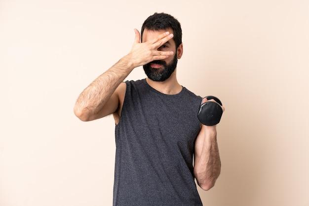 Esporte homem caucasiano com barba fazendo levantamento de peso sobre fundo isolado cobrindo os olhos pelas mãos e sorrindo