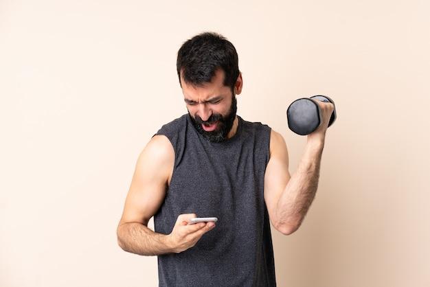 Esporte homem caucasiano com barba fazendo levantamento de peso sobre fundo isolado com telefone em posição de vitória