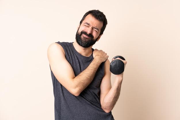 Esporte homem caucasiano com barba fazendo levantamento de peso sobre fundo isolado, sofrendo de dor no ombro por ter feito esforço