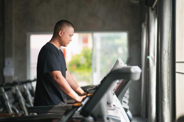 Esporte homem exercício usando andando na esteira na academia