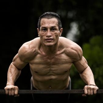 Esporte homem forte fitness modelo muscular fazendo flexões exercício em fundo preto