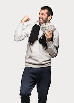 Esporte homem levando muito dinheiro sobre fundo cinza isolado