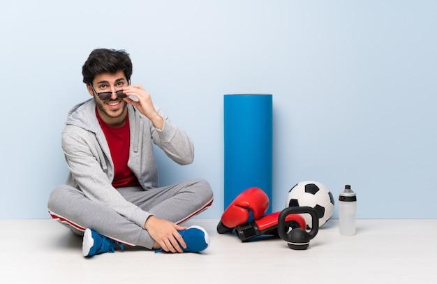 Esporte homem sentado no chão com óculos e sorrindo