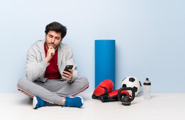 Esporte homem sentado no chão pensando e enviando uma mensagem