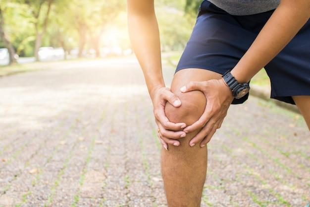 Esporte homem sofrendo de joelho e perna ferindo como exercício e treino no parque