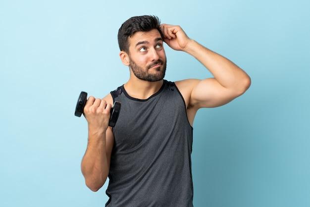 Esporte jovem com barba fazendo levantamento de peso, tendo dúvidas e com expressão facial confusa