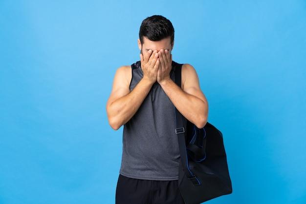 Esporte jovem com bolsa esporte isolado em um fundo azul com expressão de cansaço e enjoo