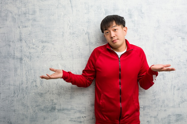 Esporte jovem fitness chinês duvidar e encolher os ombros os ombros