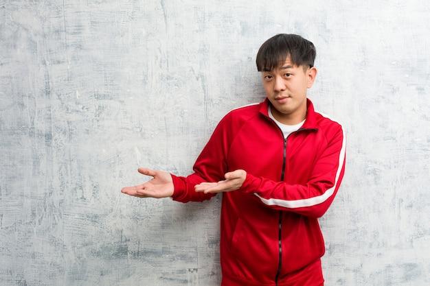 Esporte jovem fitness chinês segurando algo com as mãos
