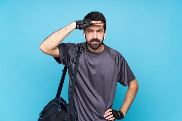 Esporte jovem homem com barba sobre azul olhando longe com a mão para procurar algo