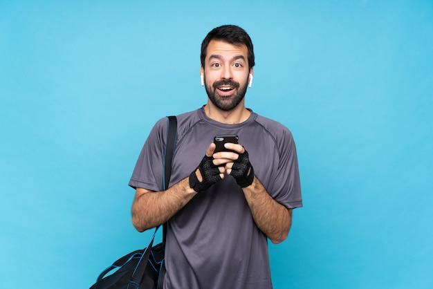 Esporte jovem homem com barba surpreso e enviando uma mensagem