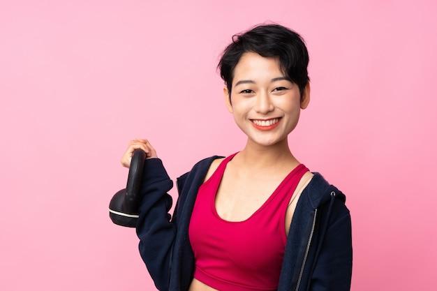 Esporte jovem mulher asiática fazendo halterofilismo com kettlebell