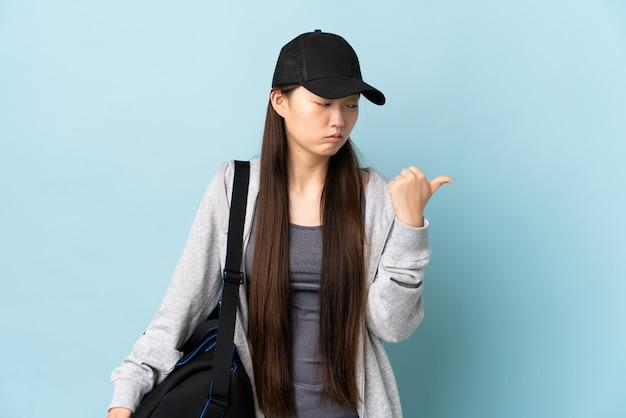 Esporte jovem mulher chinesa com saco de desporto sobre parede azul infeliz e apontando para o lado
