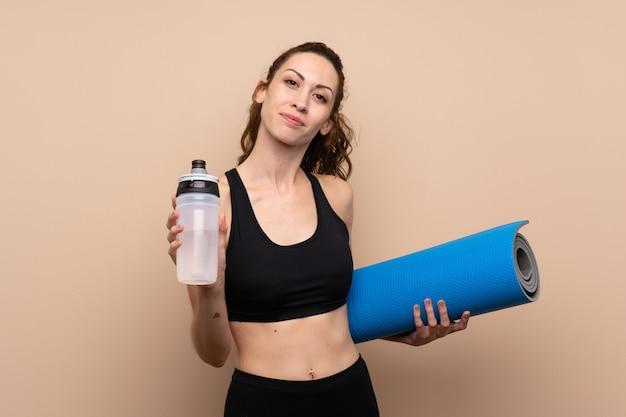Esporte jovem mulher com garrafa de água de esportes e com uma esteira