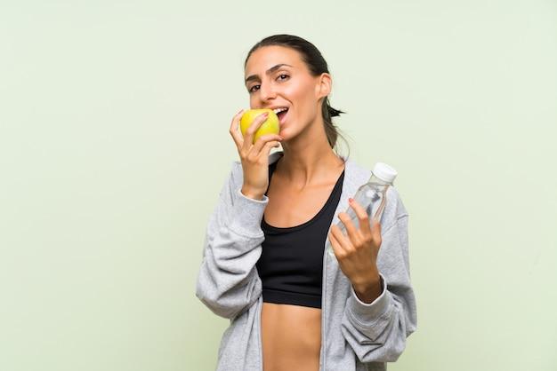 Esporte jovem mulher com uma maçã e uma garrafa de parede verde isolado de waterover