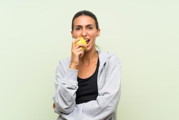 Esporte jovem mulher com uma maçã sobre parede verde isolada