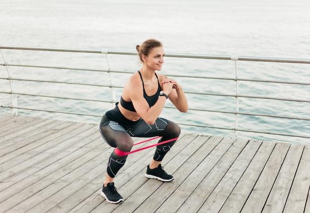 Esporte jovem mulher fazendo agachamentos com elástico no terraço da praia