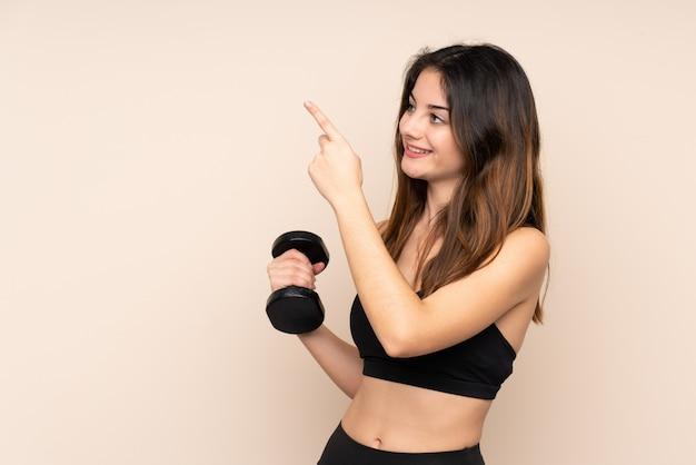 Esporte jovem mulher fazendo levantamento de peso na parede bege, apontando com o dedo indicador uma ótima idéia