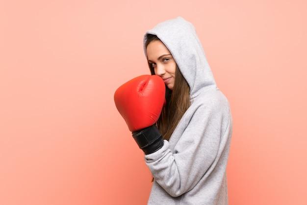 Esporte jovem mulher isolada parede rosa com luvas de boxe
