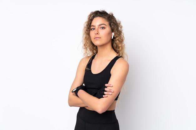 Esporte jovem mulher na parede branca, mantendo os braços cruzados
