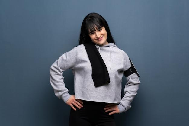 Esporte jovem mulher posando com os braços no quadril e sorrindo