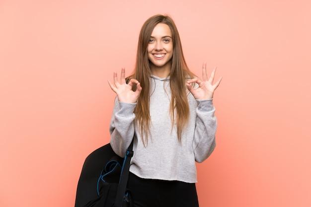 Esporte jovem mulher rosa isolada mostrando um sinal de ok com os dedos