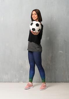 Esporte jovem mulher segurando uma bola de futebol