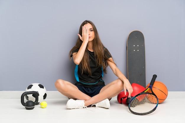 Esporte jovem mulher sentada no chão cobrindo um olho com a mão