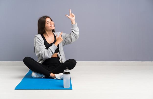 Esporte jovem mulher sentada no chão com tapete apontando com o dedo indicador uma ótima idéia