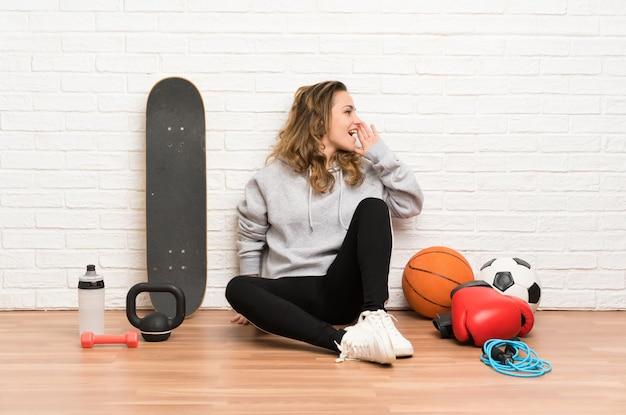 Esporte jovem mulher sentada no chão gritando com a boca aberta