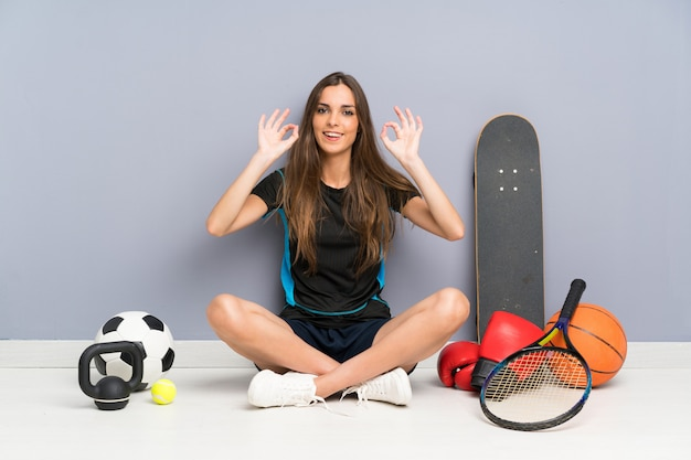 Esporte jovem mulher sentada no chão, mostrando um sinal de ok com os dedos