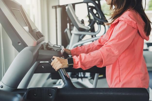 Esporte jovem mulher usando relógio inteligente correndo na esteira na academia