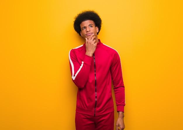 Esporte jovem negro sobre uma parede laranja duvidando e confuso