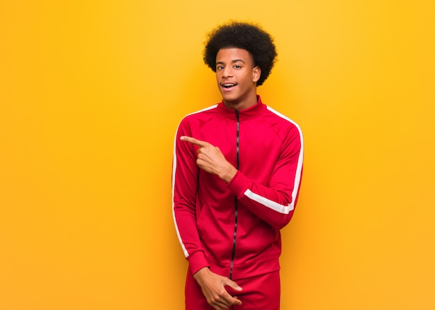 Esporte jovem negro sobre uma parede laranja, sorrindo e apontando para o lado