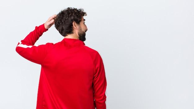 Esporte jovem vestido homem se sentindo confuso e confuso enquanto coça a cabeça e olhando para o lado