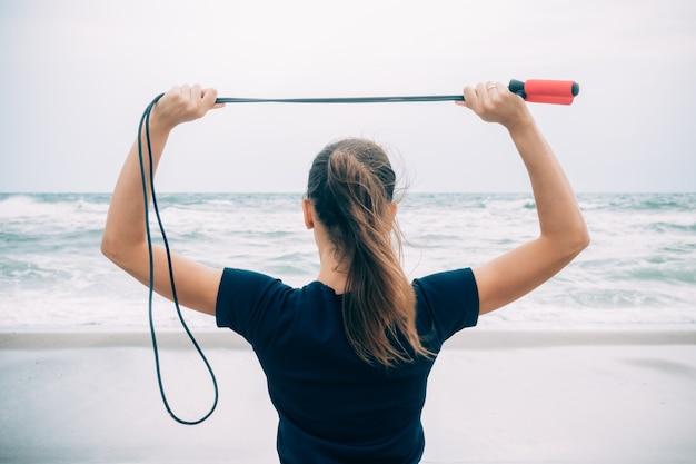 Esporte menina morena em pé na praia e segurando uma corda de pular sobre a cabeça