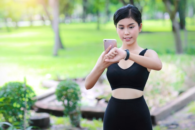 Esporte menina segurando o telefone inteligente e verificando o relógio inteligente