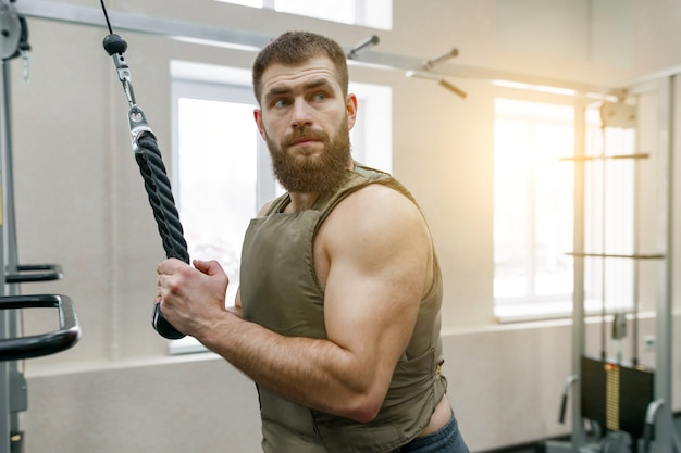 Esporte militar, homem adulto barbudo caucasiano muscular fazendo exercícios
