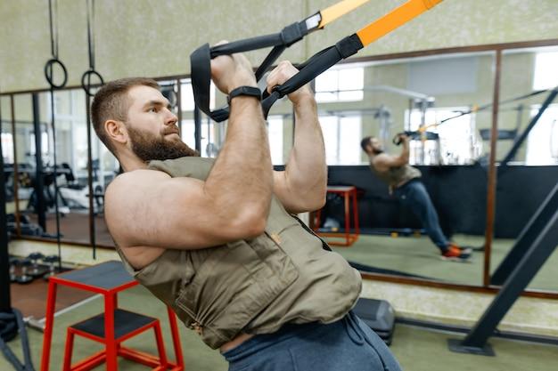Esporte militar, homem adulto barbudo muscular fazendo exercícios