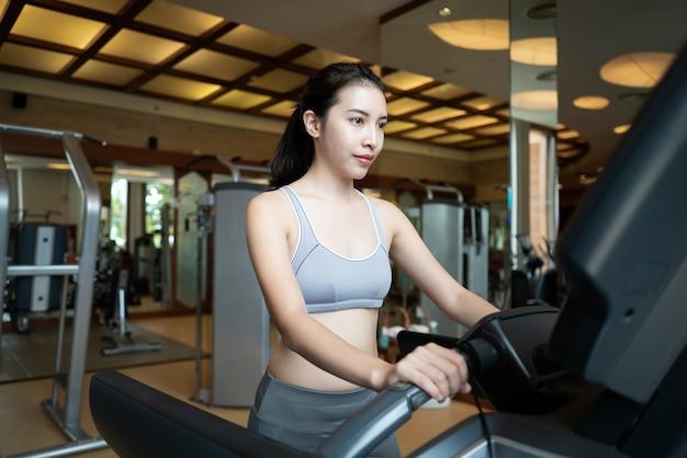 Esporte mulher andar na máquina de cardio na academia