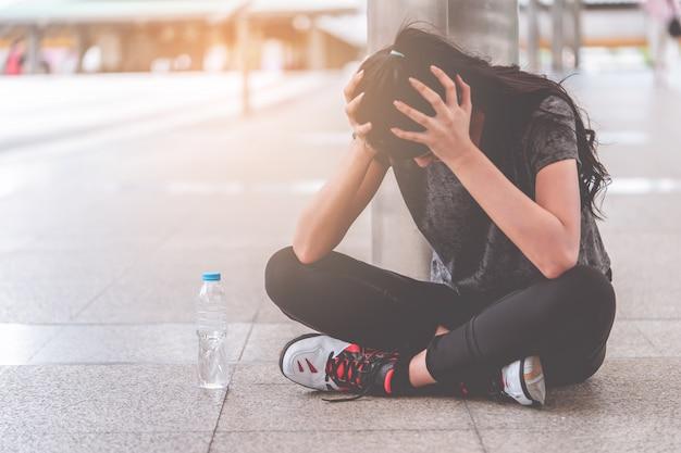 Esporte mulher com a mão na cabeça dela tendo dor de cabeça