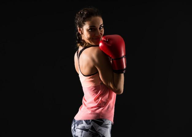 Esporte mulher em fundo escuro com luvas de boxe