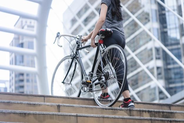 Esporte mulher está carregando sua bicicleta até a escada
