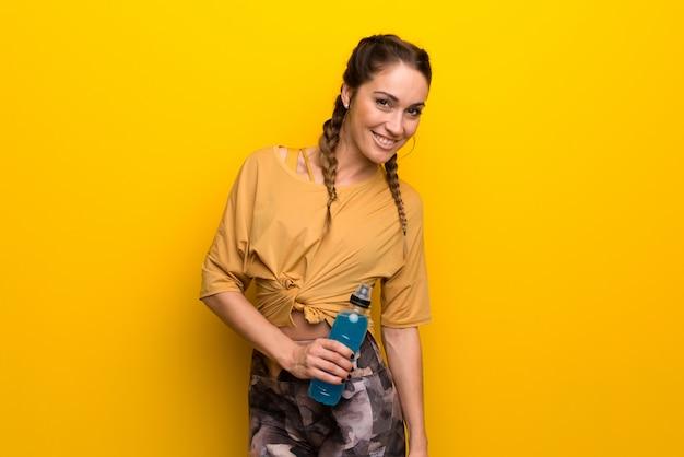 Esporte mulher no fundo amarelo vibrante com uma garrafa