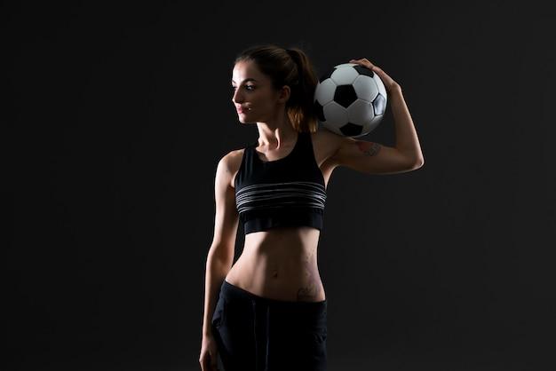 Esporte mulher no fundo escuro, segurando uma bola de futebol