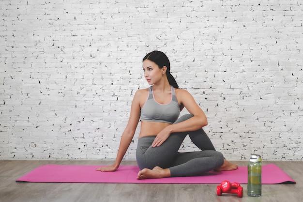 Esporte mulher sentada relaxar no tapete rosa e fazer exercícios de fitness com garrafa de água em casa. conceito de dieta. fitness e estilo de vida saudável